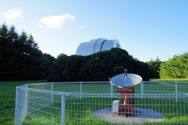 パラボラアンテナと天文機器資料館のかまぼこ型の屋根、そして青い空のコラボが絵になります