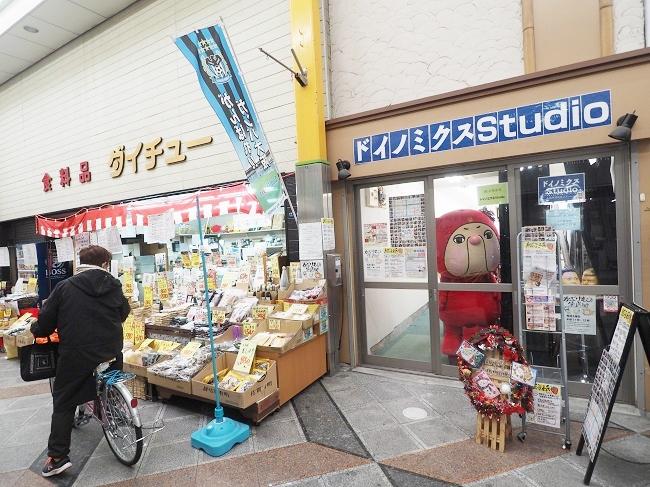 アーケード商店街のなかにあるコミュニティスペース「ドイノミクスStudio」。外を覗いているのは、ゆるキャラ「メガ佐藤」くん