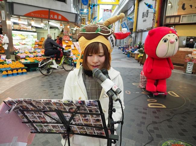 たこ焼きのかぶりもの姿で取材したてのセール情報を話す「おしゃべりアーティスト」の上田瑞穂さん