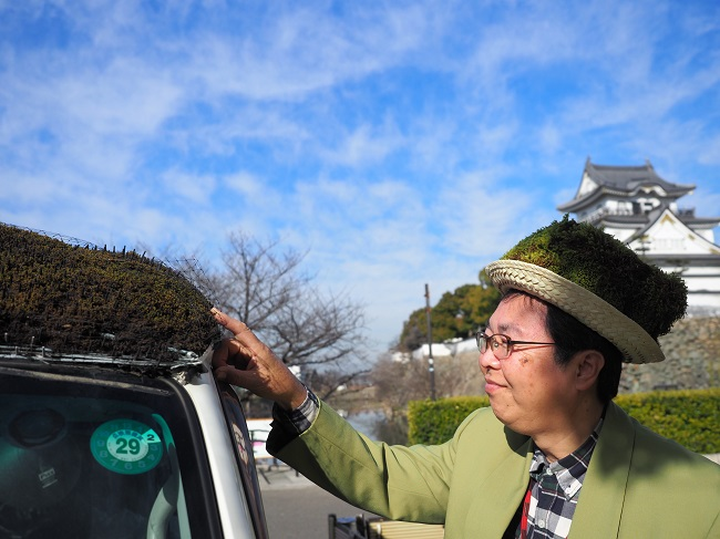 環境緑化の大切さを視覚からメッセージする愛車「やあね、こけちゃっカー」。いつくしむように見つめる泉原さん